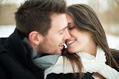stock photo of cheer-up  - Attractive heterosexual couple kissing on a blanket in the snow - JPG