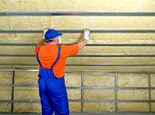stock photo of attic  - Construction worker thermally insulating house attic with mineral wool - JPG
