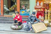 HANOI, VIETNAM, JANUARY 13, 2013 - an artisan is painting a carved table sitting on street while a w