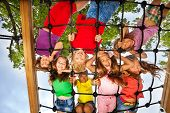 pic of playground  - Many kids look though gridlines of playground and smile happily - JPG