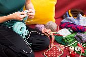 pic of knitting  - closeup of a knitting woman sitting on a couch - JPG
