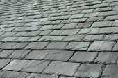picture of slating  - Part of roof showing overlapping grey / green slate tiles