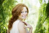 stock photo of redhead  - Portrait of redhead girl with blue eyes on nature - JPG