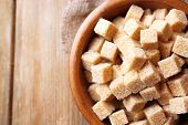 stock photo of sugar cube  - Brown sugar cubes and crystal sugar in bowl on wooden background - JPG