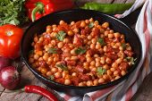 pic of tripe  - Chickpeas with chorizo in a frying pan and the ingredients on the table close - JPG