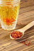 picture of saffron  - Spoon dry saffron on a background a glass with the infusion of saffron - JPG
