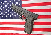 picture of mayhem  - View of automatic pistol set on US flag - JPG
