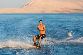 foto of watersports  - Wakeboarder in colorful shorts riding in sunset - JPG