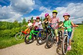 Постер, плакат: Children in row wearing helmets holding bikes