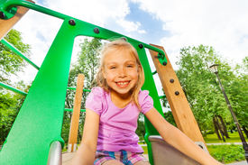 image of chute  - Portrait of funny smiling small girl on playground chute looking straight - JPG