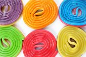 stock photo of licorice  - some licorice wheels of different colors on a white background - JPG