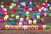 picture of investigation  - Sign INVESTIGATION and many colored cubes with letters on wooden table - JPG