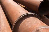 pic of orifice  - Rusty metal pipes stack on the construction site - JPG