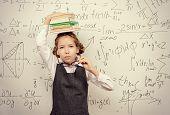 picture of schoolgirl  - Pretty smart schoolgirl in big glasses stands with books at the blackboard - JPG