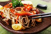 pic of chinese parsley  - Chinese noodles with vegetables and roasted meat on plate on bamboo mat background - JPG