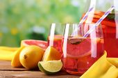 stock photo of pitcher  - Pink lemonade in glasses and pitcher on table on natural background - JPG