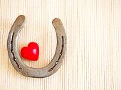 stock photo of baste  - Horseshoe and heart on a background of bast fibers - JPG