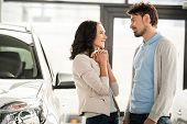 stock photo of rental agreement  - Beautiful young couple in the showroom choosing a car - JPG