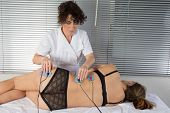 picture of hernia  - woman is doing massage of electrostimulator for the spine - JPG