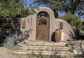 stock photo of front-entry  - Stylish stucco rustic wood door archway entrance with steps to luxury home - JPG