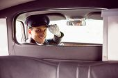 picture of partition  - Limousine driver smiling at camera through partition in limousine - JPG