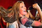 pic of karaoke  - Happy blonde singing karaoke into mic in a bar - JPG