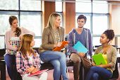 stock photo of student teacher  - Happy students talking with their teacher in the library - JPG