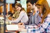 picture of classmates  - Student looking at camera while studying with classmates in library - JPG