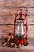 picture of kerosene lamp  - Kerosene lamp with cones ans walnuts on wooden planks background - JPG