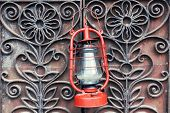 stock photo of kerosene lamp  - Kerosene lamp on wrought iron gates background - JPG