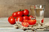 pic of ouzo  - Glasses of ouzo and tomatoes on wooden table - JPG