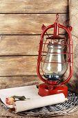 foto of kerosene lamp  - Kerosene lamp with dried rose and letter on wicker mat and wooden planks background - JPG
