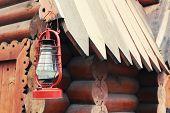 stock photo of kerosene lamp  - Kerosene lamp hanging on wooden house - JPG