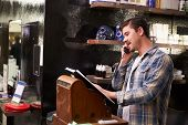 picture of cash register  - Male Barber Standing By Cash Register Taking Booking - JPG