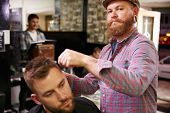 pic of facial piercings  - Portrait Of Male Barber Giving Client Haircut In Shop - JPG