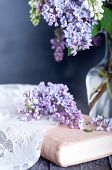stock photo of hazy  - Bouquet of purple lilac spring flowers with an open book and vintage hazy editing - JPG