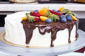 pic of kumquat  - Cake with strawberries, blueberries, kumquat drizzled with chocolate ** Note: Visible grain at 100%, best at smaller sizes - JPG