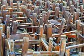 picture of upside  - Pile of old restaurant chairs turned upside down after working hours - JPG