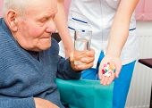 stock photo of kindness  - Elderly man in wheelchair taking several medicine from kind nurse - JPG