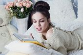 stock photo of short-story  - Girl reading a book with interest in the room - JPG