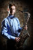 foto of saxophones  - Portrait of a musician with his saxophone - JPG