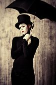 stock photo of mime  - Portrait of a male mime artist standing under umbrella expressing sadness and loneliness - JPG