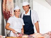 stock photo of slaughterhouse  - Portrait of confident female butcher cutting meat while standing by male colleague at counter in shop - JPG