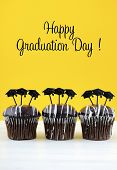 pic of graduation hat  - Happy Graduation Day party chocolate cupcakes with graduation cap hat topper decorations in yellow black and white party theme - JPG