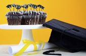 foto of graduation hat  - Happy Graduation Day party chocolate cupcakes with graduation cap hat topper decorations in yellow black and white party theme - JPG