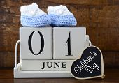 picture of booty  - International Childrens Day concept with June First Calendar and child booties on dark wood rustic background - JPG
