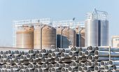 picture of silos  - Plastic tubes for pipelines with the background of chemical plant silos - JPG