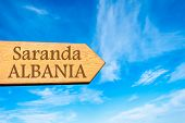 picture of albania  - Wooden arrow sign pointing destination SARANDA ALBANIA against clear blue sky with copy space available - JPG
