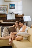 image of  preteen girls  - Preteen girl and her mother watching something on laptop - JPG