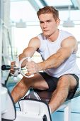 stock photo of concentration man  - Concentrated young man working out in gym - JPG